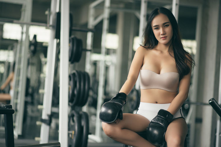 Portrait Of Confident Young Woman With Boxing Gloves Sitting On Stool In Gym