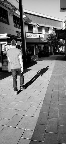 Candid shot. Not the most sexiest of settings, just thought the long shadow cast by the passerby was pretty cool. Blackandwhite Black And White One Person One Man Only City Architecture Building Exterior Built Structure The Mobile Photographer - 2019 EyeEm Awards The Street Photographer - 2019 EyeEm Awards