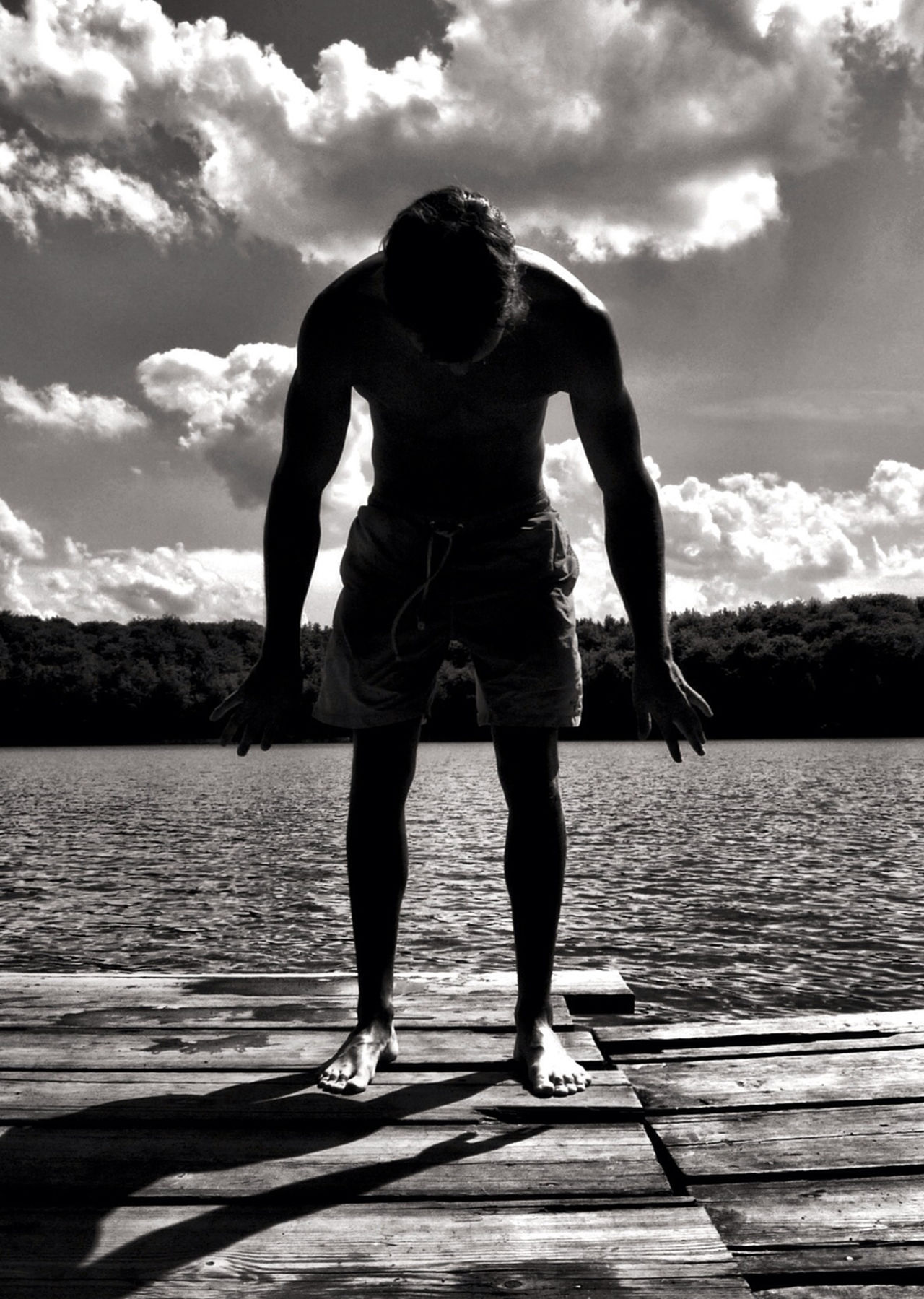 Full length of a man standing on jetty against lake