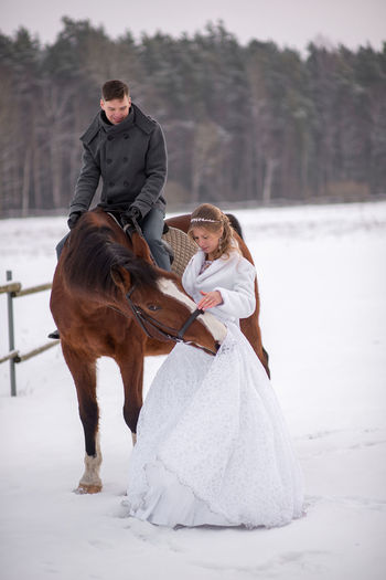 Smiling groom looking at bride touching on snow covered field