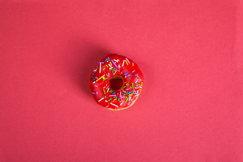 High angle view of multi colored candies against red background