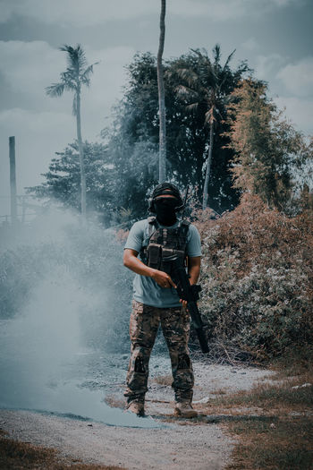 Man with gun airsoft standing on land against sky