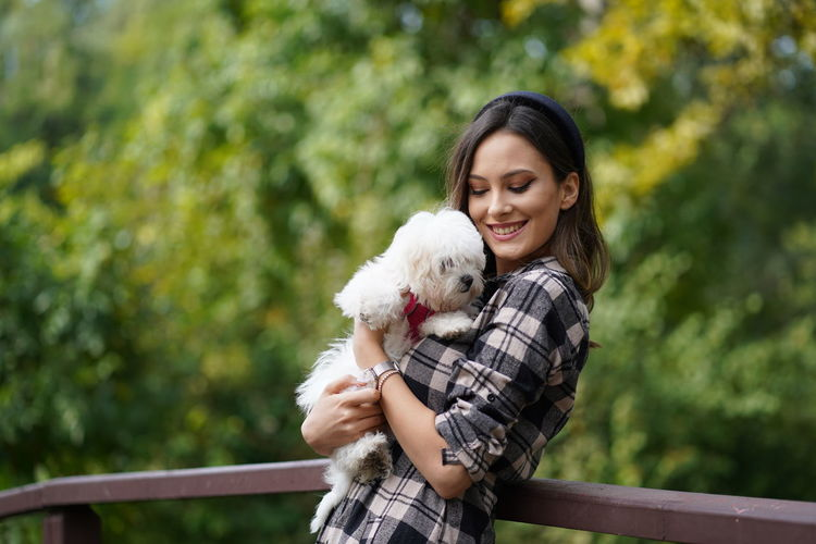 Young smiling woman holding dog standing at park