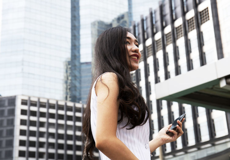 Smiling young woman holding mobile phone while standing in city