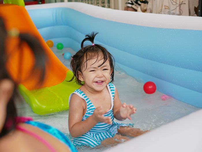 Portrait of cute girl sitting in wading pool