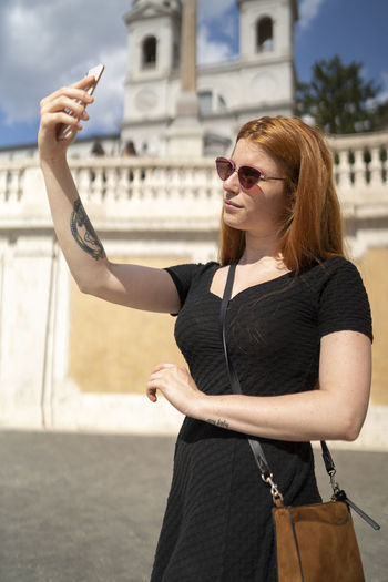 Young woman wearing sunglasses standing against city in background