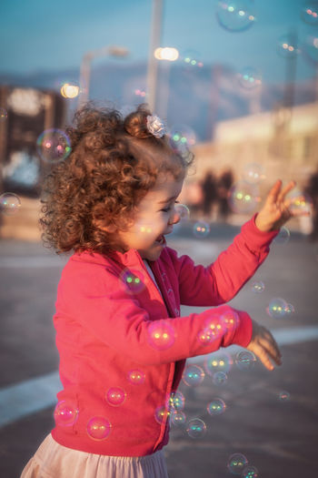 Side view of girl standing amidst bubbles at night