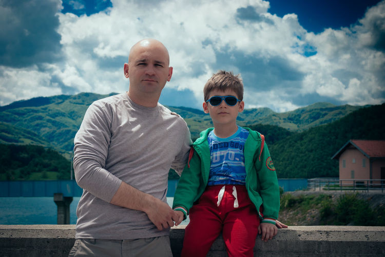 Portrait of father and son on bridge against mountains and sky