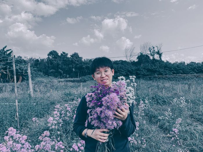Portrait of smiling woman standing on purple flowering plants