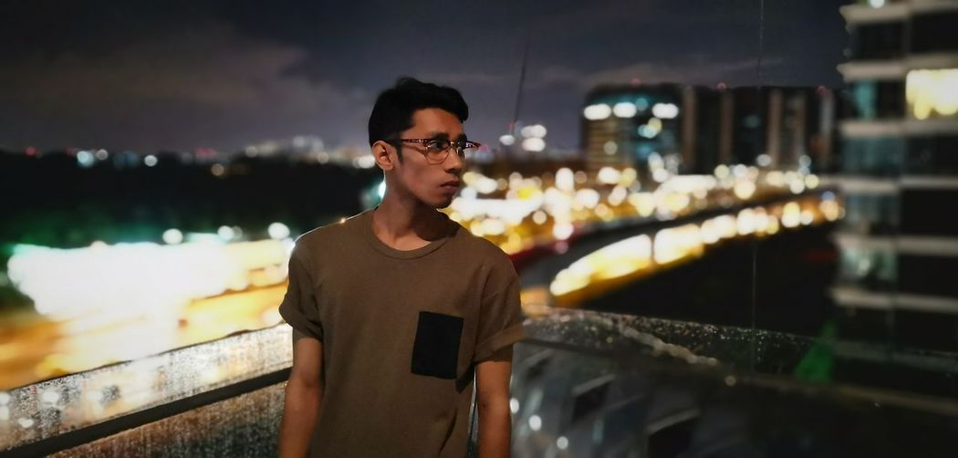 Thoughtful young man looking away while standing against illuminated city at night
