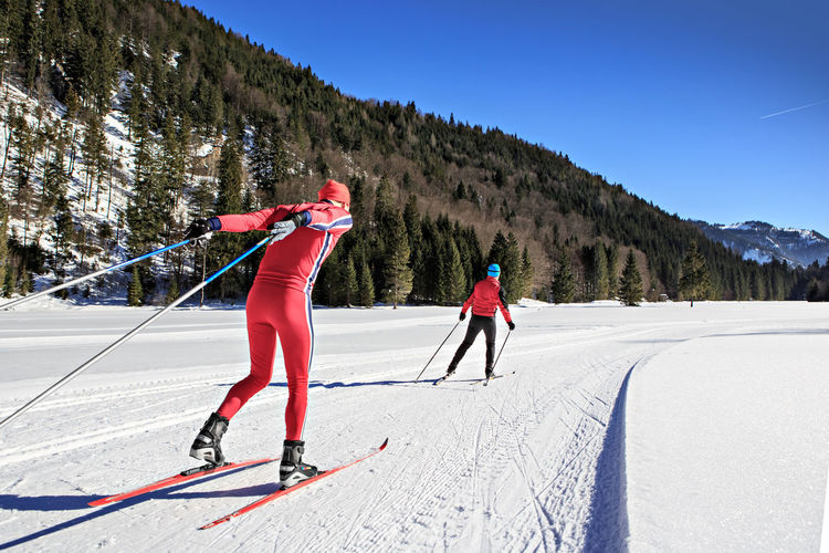 Rear View Of Men Skiing On Field Against Mountain