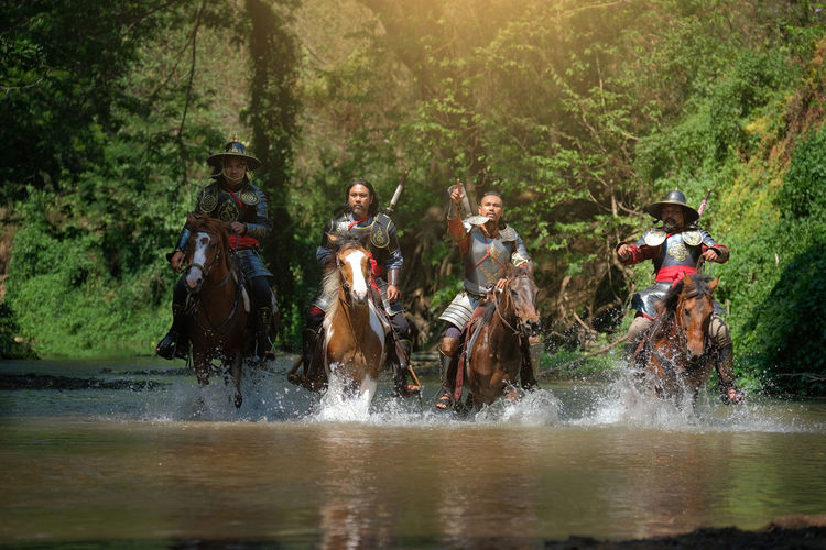 Male warriors riding horses in lake at forest