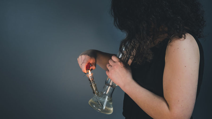 Midsection of woman smoking hookah against white background