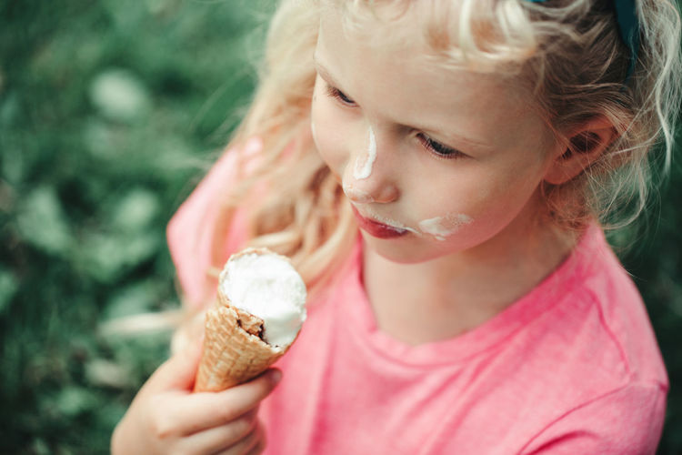 Cute funny girl with dirty nose and milk moustaches eating licking ice cream from waffle cone