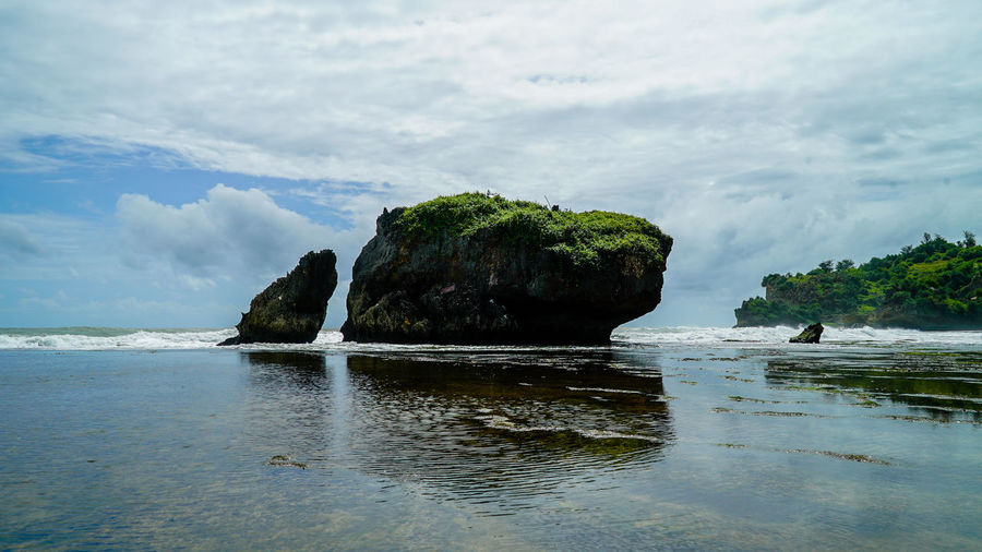 Scenic view of rock formation on sea against cloudy sky