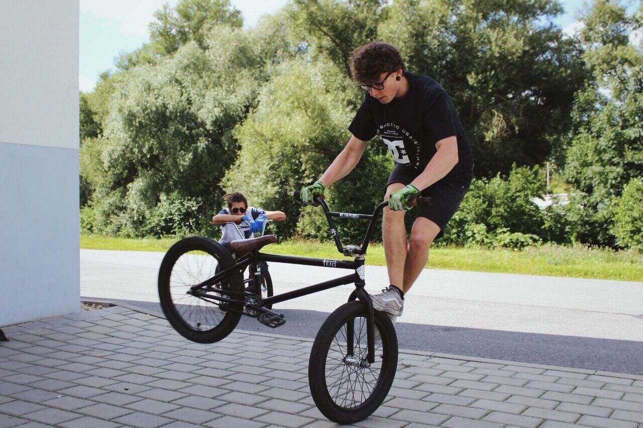 YOUNG MEN SITTING ON BICYCLE IN PARK
