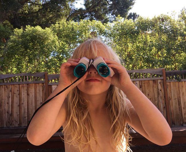 Close-up of topless girl using binoculars