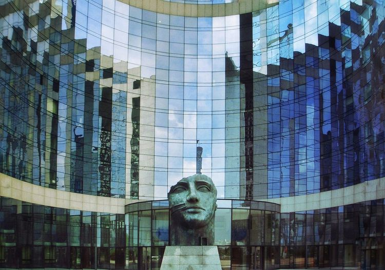 Reflection Of Statue In Modern Glass Building