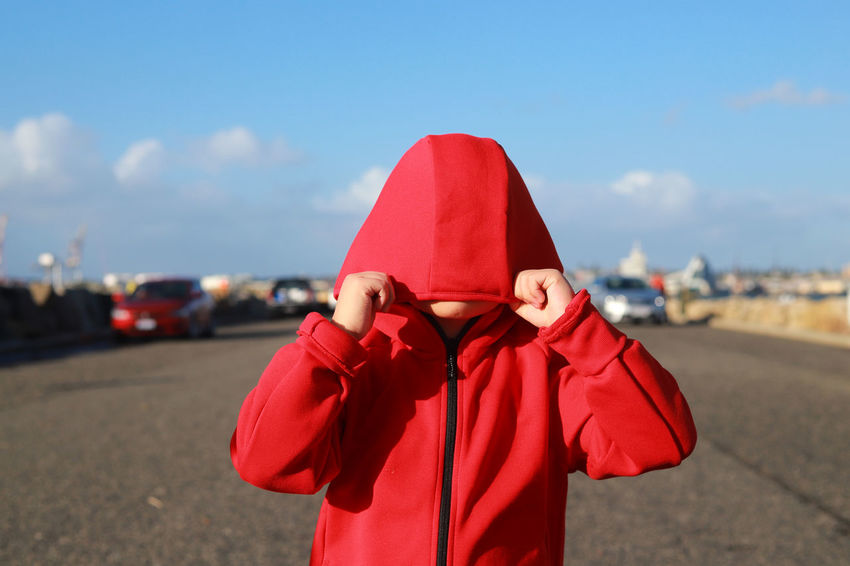 Little shy boy hides his face in the hood Boy Casual Clothing Clothing Day Focus On Foreground Front View Holding Hood - Clothing Leisure Activity Lifestyles Nature Obscured Face One Person Outdoors Real People Red Shy Sky Standing Transportation Unrecognizable Person Waist Up