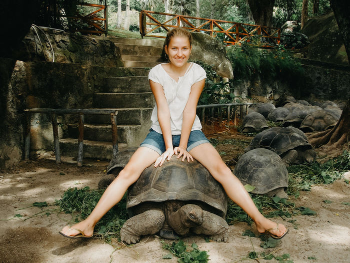 Woman sitting on the giant tortoise