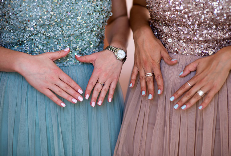 Midsection of women showing their nail polishes on fingernails