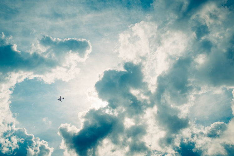 Low angle view of airplane flying in cloudy sky