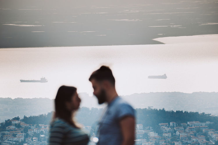 People standing by cityscape in city against sky