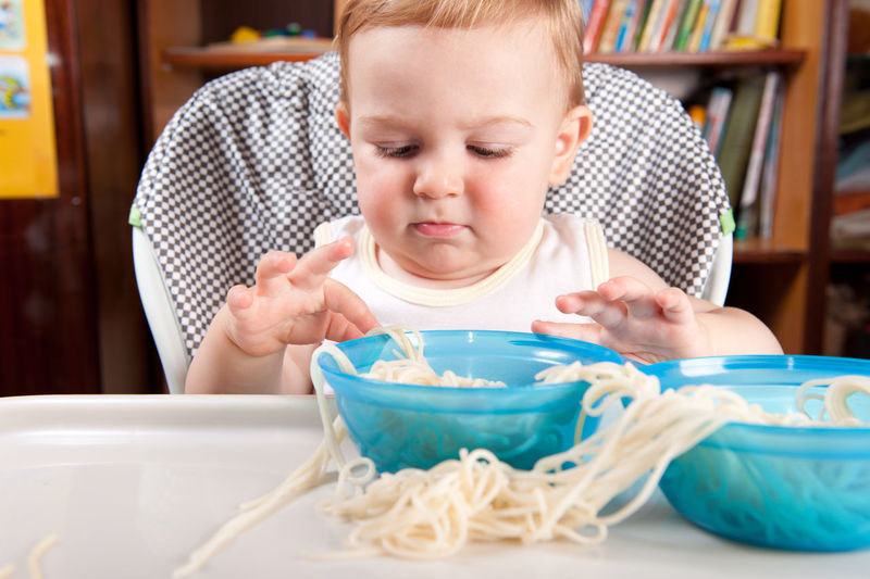 Close-up of baby boy with pasta on table