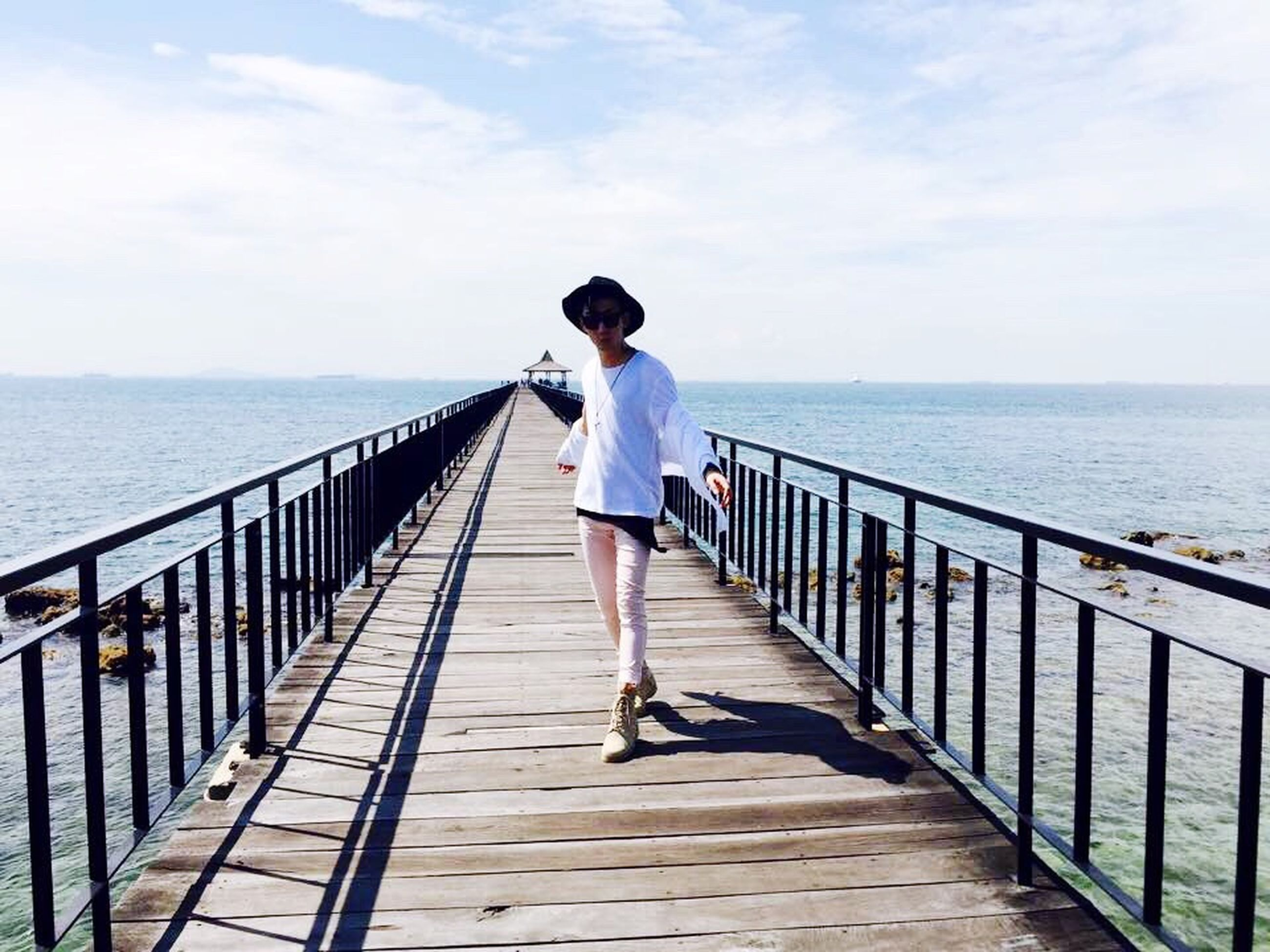 full length, railing, water, sea, rear view, pier, sky, casual clothing, lifestyles, the way forward, standing, leisure activity, walking, horizon over water, tranquility, nature, tranquil scene, wood - material