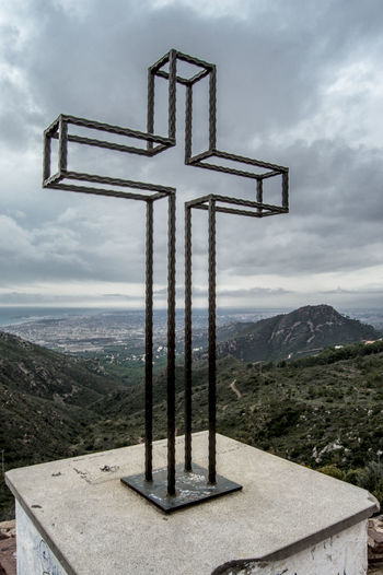 Close-up of metallic cross overlooking mountains against cloudy sky