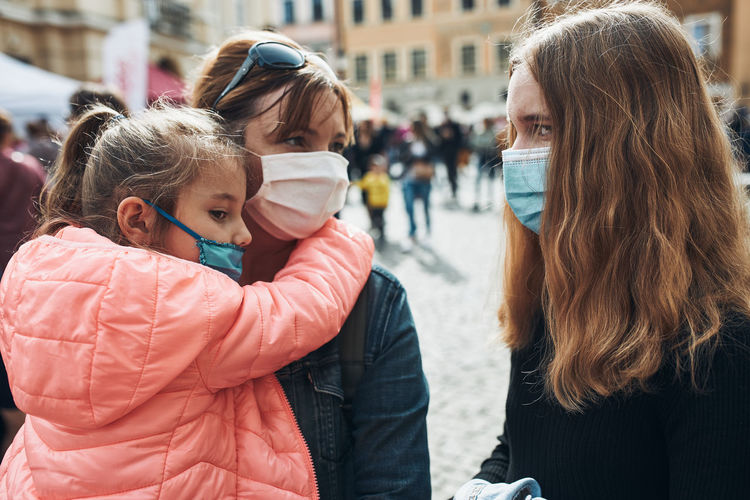 Family mother and her daughters standing in a street downtown wearing the face masks to avoid virus