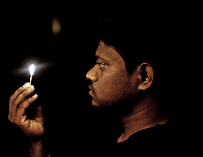 Young man holding burning matchstick at night