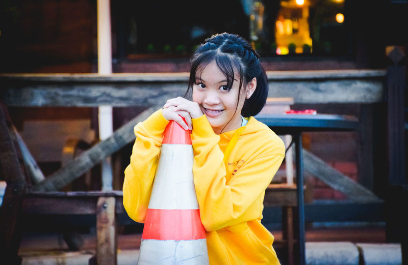 Portrait Of Smiling Young Woman Holding Traffic Cone While Standing At Roadside