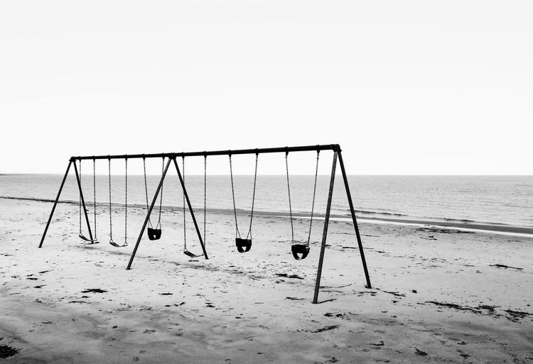 View of swing on beach against clear sky