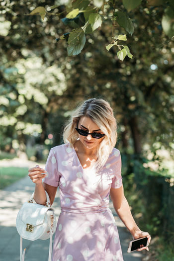 Young woman wearing sunglasses standing on footpath