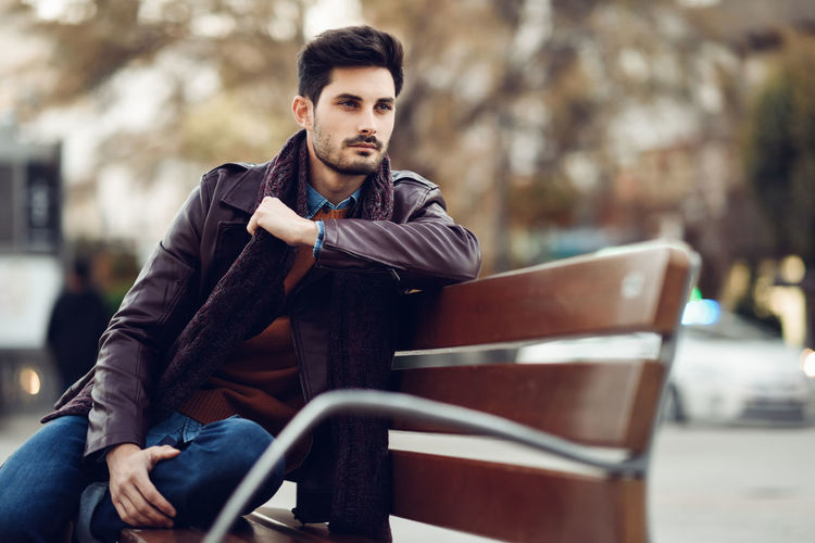 Thoughtful young man sitting on an urban bench. Attractive guy with modern hairstyle with lost look in the street. Bench Fashion Man Attractive Beautiful People Clothing Contemplation Day Focus On Foreground Handsome Leisure Activity Lifestyles Looking Looking At Camera Men One Person Outdoors Portrait Real People Seat Sitting Three Quarter Length Young Adult Young Men