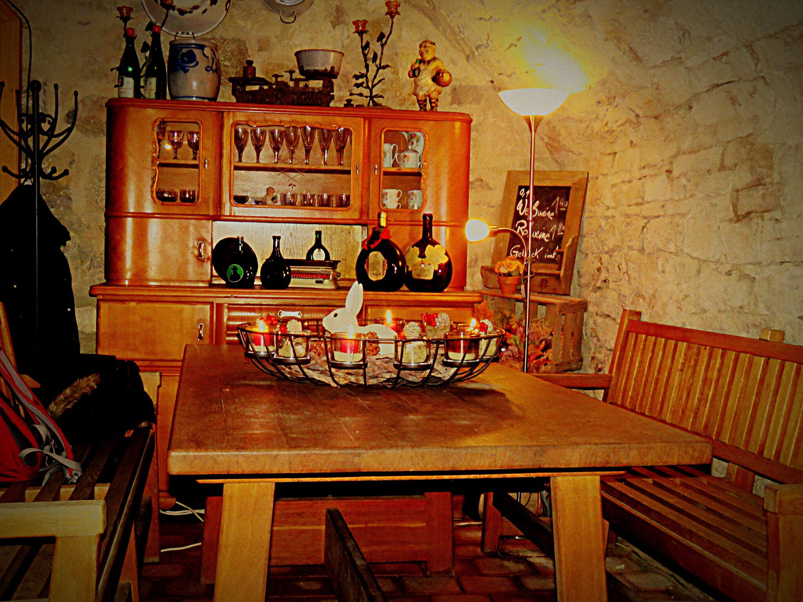 indoors, table, text, chair, wood - material, communication, illuminated, home interior, absence, wall - building feature, built structure, furniture, hanging, architecture, no people, western script, lighting equipment, house, non-western script, restaurant