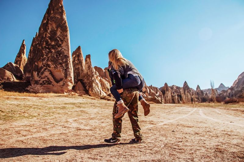 Full length of man standing on rock formation against clear sky