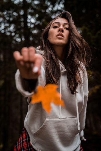 Portrait of beautiful young woman standing against orange