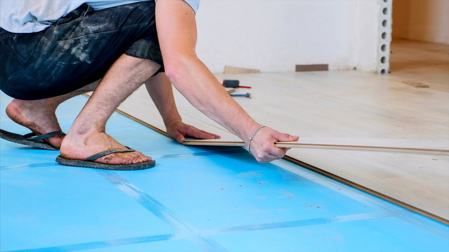 Low section of man measuring plank in workshop