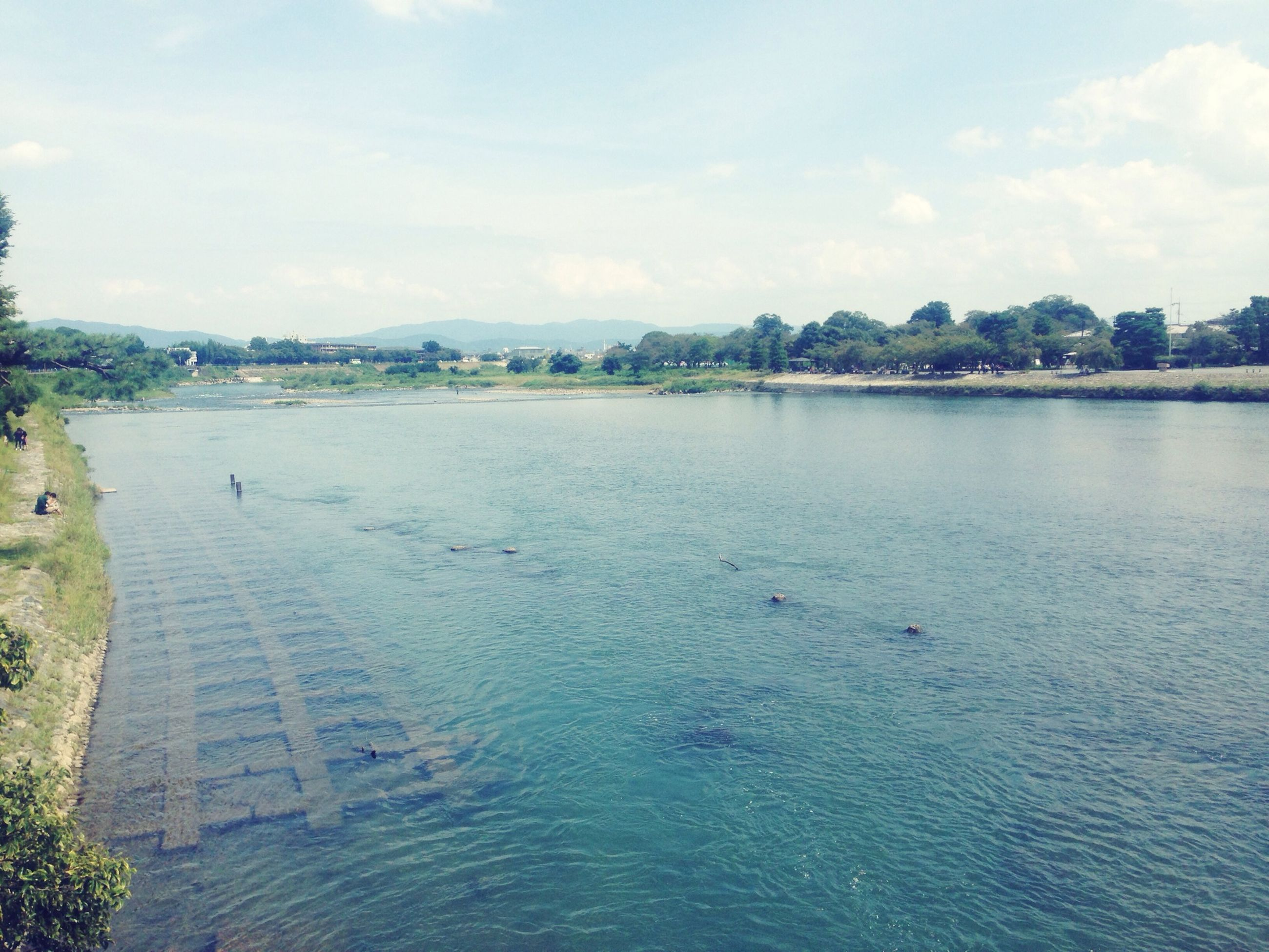 water, sky, waterfront, building exterior, built structure, architecture, cloud - sky, tranquil scene, tree, scenics, rippled, tranquility, river, nature, cloud, sea, lake, beauty in nature, day, outdoors
