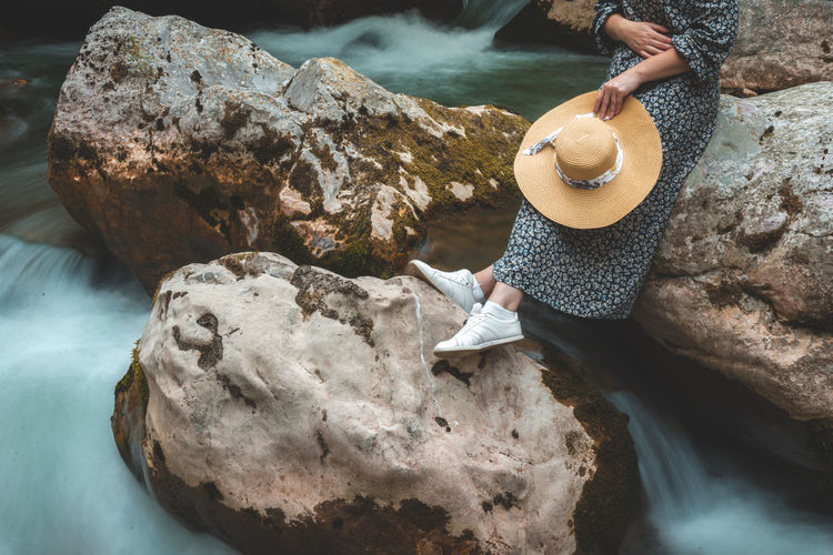 Woman relaxing on the river rocks with hat in summer