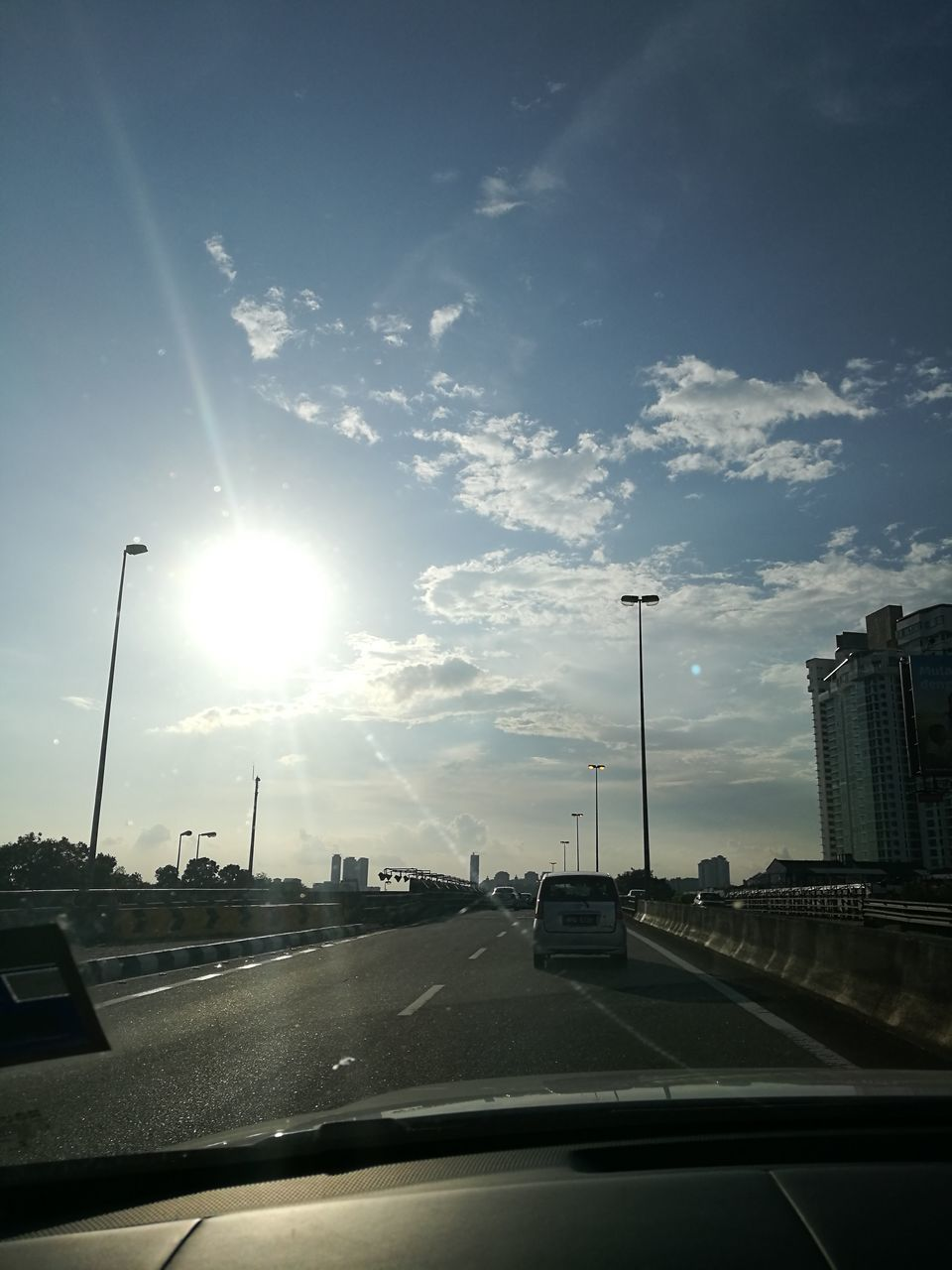 car, transportation, land vehicle, vehicle interior, mode of transport, car interior, sky, windshield, road, sunbeam, sun, cloud - sky, car point of view, sunlight, no people, built structure, day, city, architecture, sunset, outdoors, nature