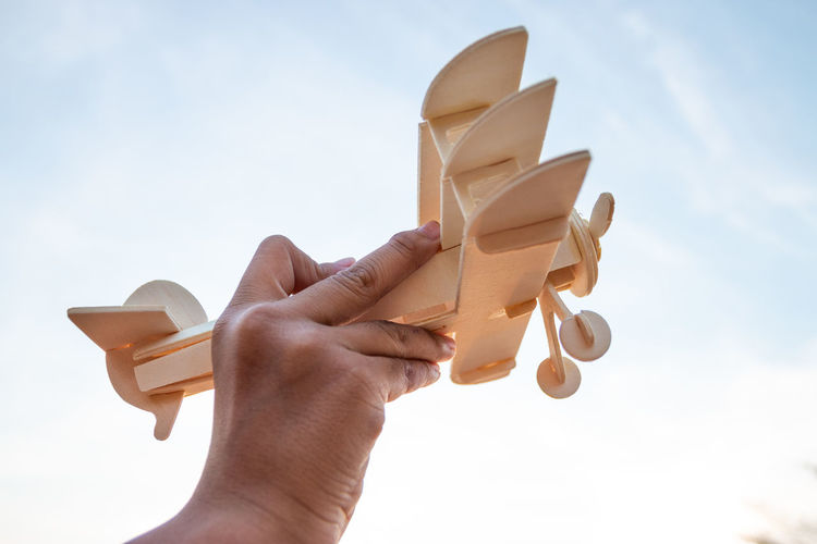 Low angle view of hand holding toy against sky