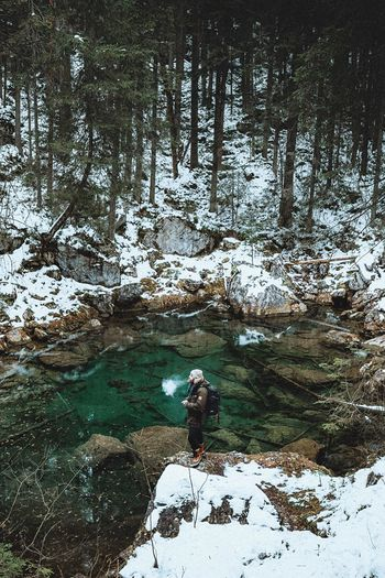 Man standing on rock by pond in forest during winter