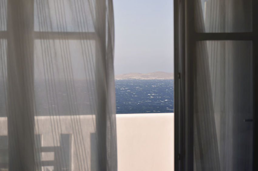 View from Balcony in Mykonos, Greece Balcony View Architecture Balcony Beauty In Nature Built Structure Curtain Day Glass - Material Indoors  Mountain Mykonos Nature No People Scenics - Nature Sea Sky Sunlight Transparent Water Window The Traveler - 2018 EyeEm Awards The Great Outdoors - 2018 EyeEm Awards
