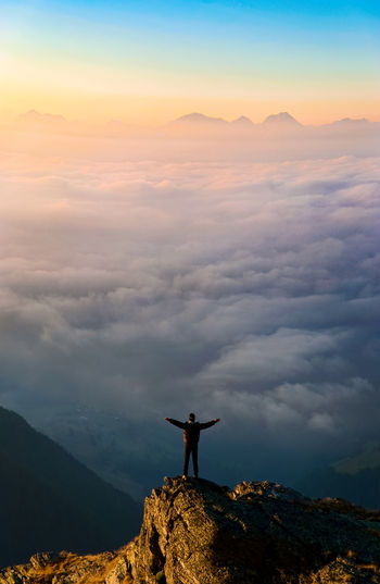 Man standing on rock against sky at sunset