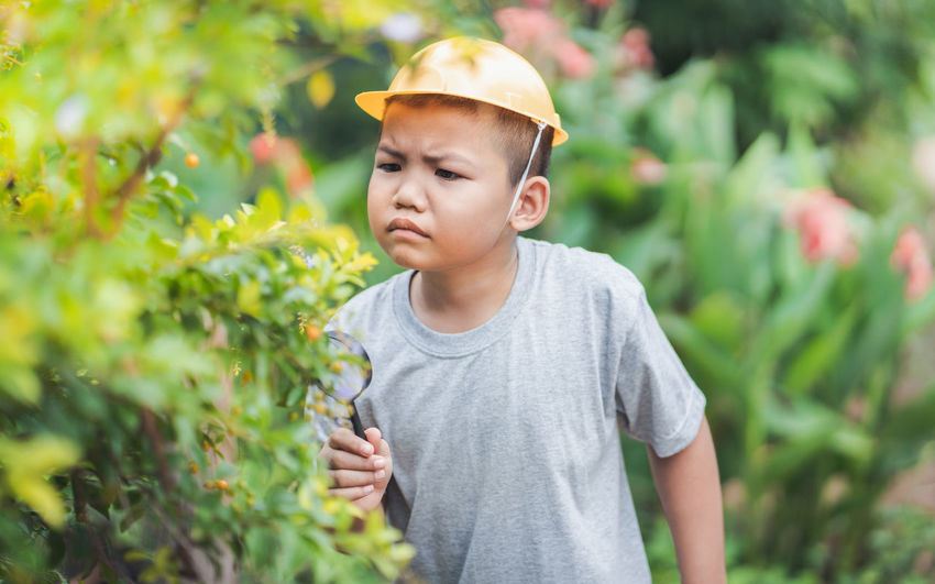 Boy looking away while standing against plants