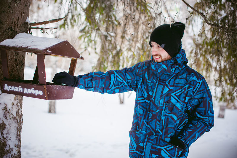 Young man standing by bird feeder on tree during winter