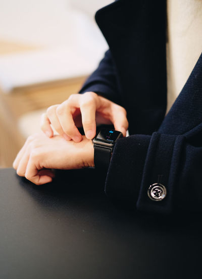 Midsection of person using smart watch on table